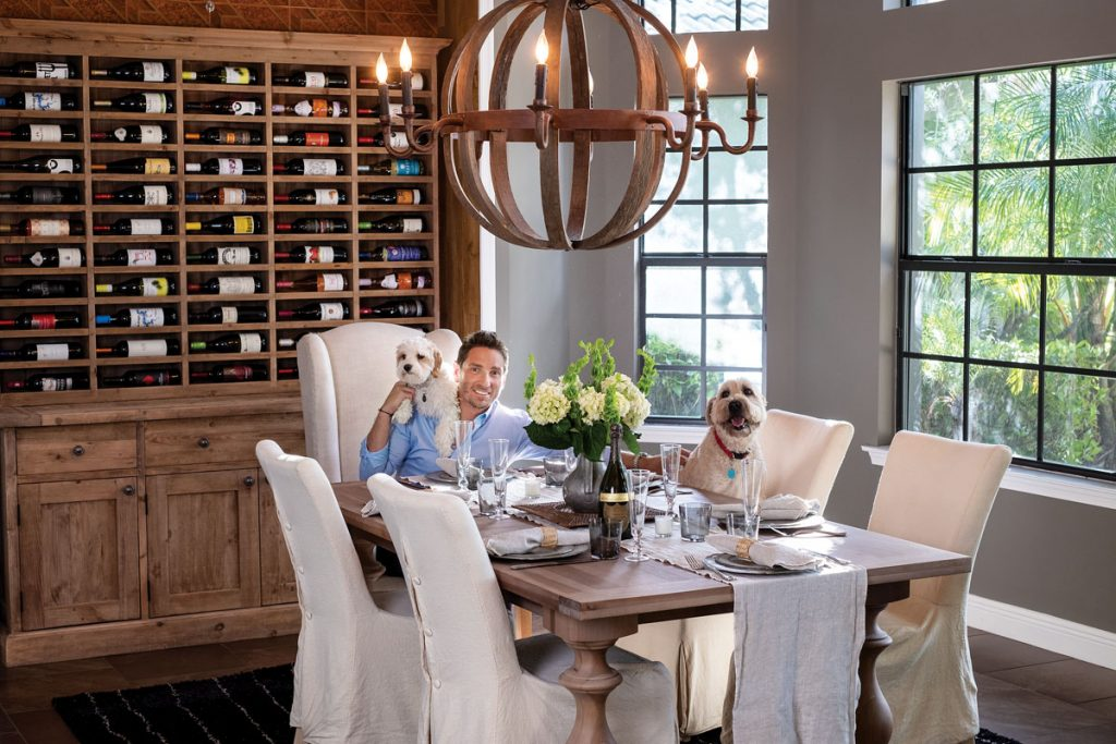 Gluck with his dogs, Uzi and Ryder, in the dining room.