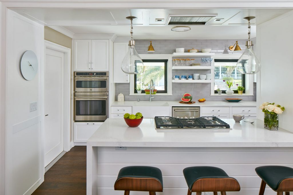 The airy, open kitchen features custom cabinetry, wide-plank wood floors, and pendant lighting