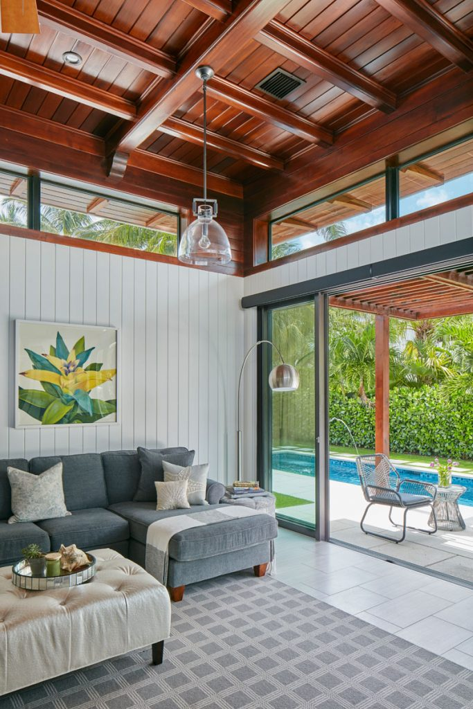 The lofty sunroom features cedar ceilings, ceramic flooring, and V-groove paneling (artwork behind the sofa is from Z Gallerie in Palm Beach Gardens).