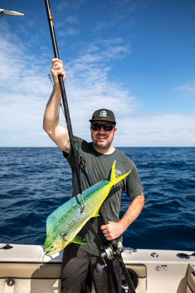 Nickey holds up his prized catch of the day: a 22-inch mahi-mahi, which he'll use to prepare a meal for his family.