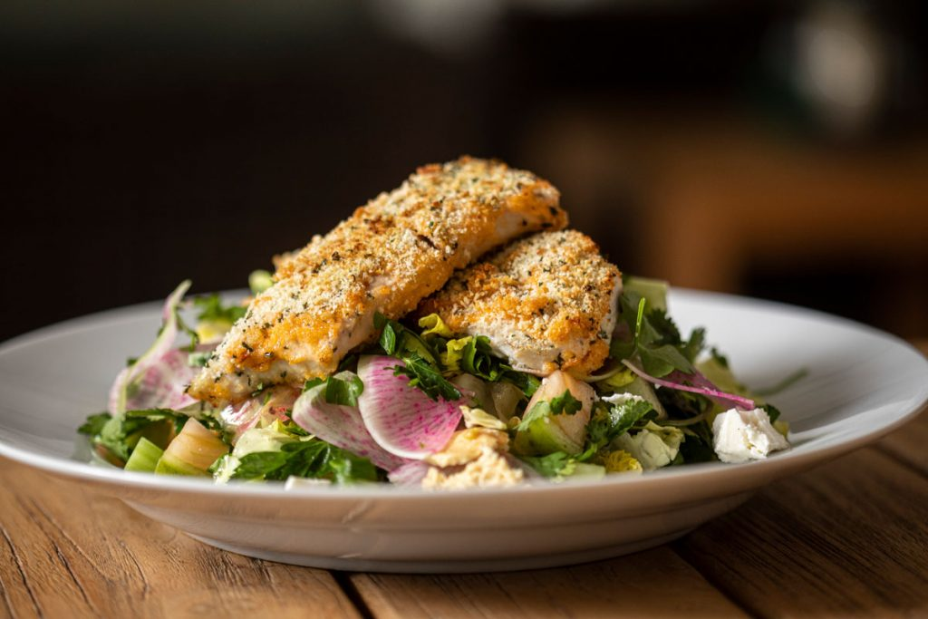 Garlic and herb–crusted local mahi-mahi and Middle Eastern fattoush salad. Photography by Benjamin Rusnak