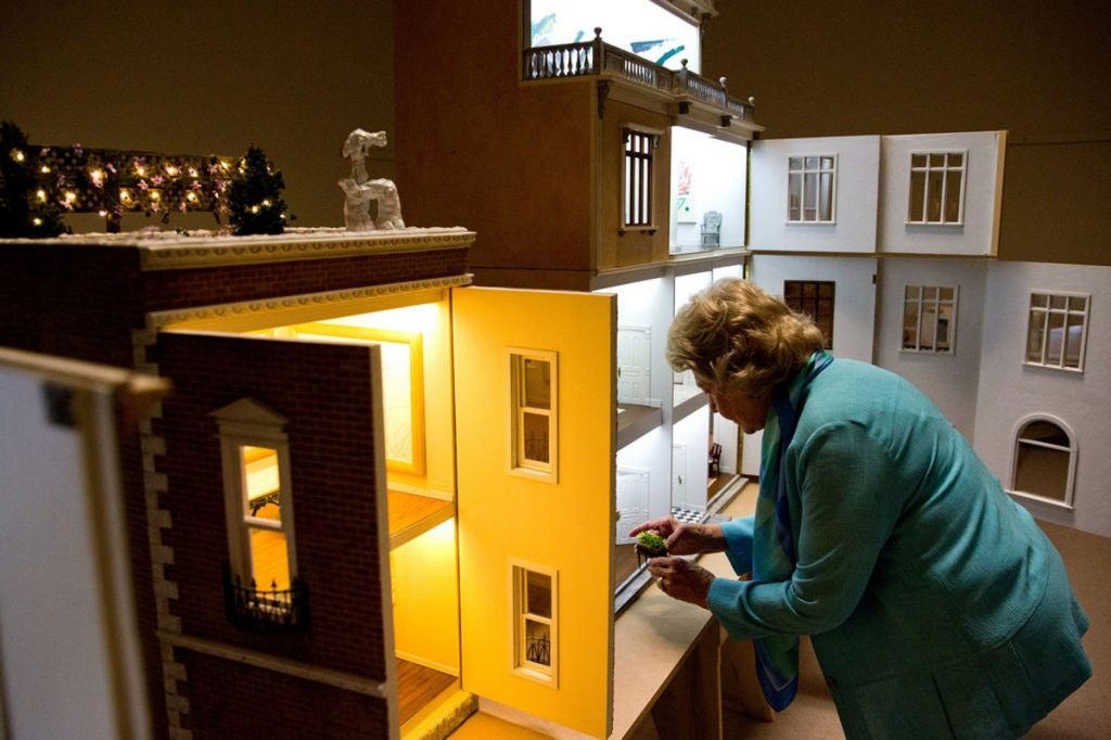 Lucy Bassett Andrews with her dollhouses, on view beginning June 7. Image courtesy of Lighthouse ArtCenter