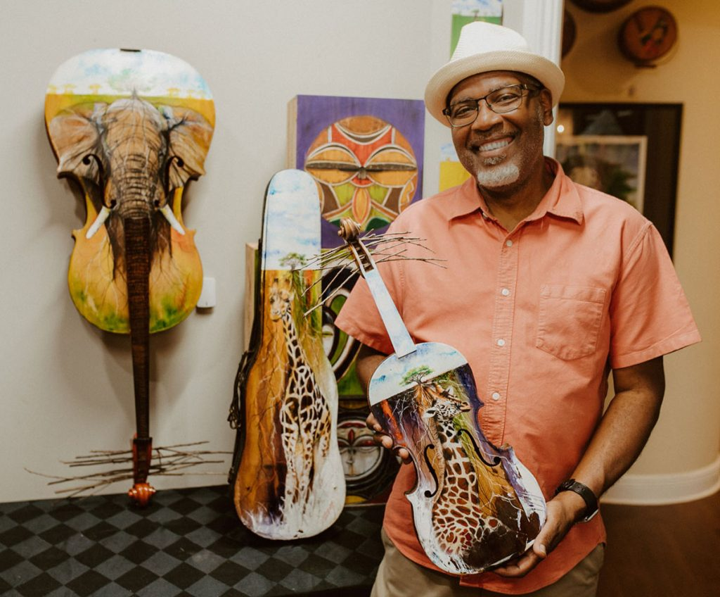 """Anthony Burks with his artwork for """"Musical Masterpieces."""" Photos courtesy of Palm Beach Symphony"""